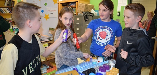 Two fifth-grade girls and two fifth-grade boys discuss which deodorants to add to their boxes of personal care items, which they are assembling as part of the Tioga Hills Elementary School's Fifth-grade Community Box Project