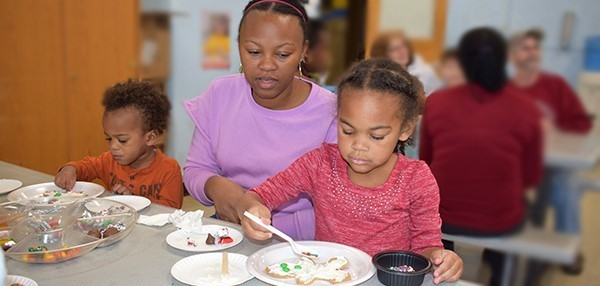 A girl in the Universal Pre-Kindergarten program at the Cub Care campus carefully shakes sprinkles over her frosted gingerbread man cookie next to her mother and little brother during one of the Cookie Decorating parties on December 20, 2018