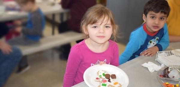 A girl and a boy in the Universal Pre-Kindergarten program at the Cub Care campus display their wonderfully decorated gingerbread men cookies at the end of the Cookie Decorating party on December 20, 2018