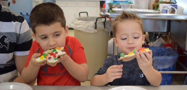 Two Universal Pre-Kindergarten boys bite into the gingerbread cookies they decorated during the family-inclusive Cookie-Decorating Party at the Cub Care campus on December 20, 2018