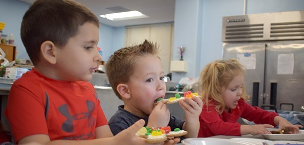 A boy bites into a gingerbread cookie he decorated with frosting and lots and lots of gumballs during the Cookie Decorating party at the Universal Pre-K at Cub Care