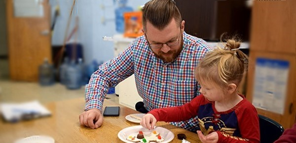 A father oversees as his daughter, a student in the Universal Pre-Kindergarten program at the Cub Care campus, carefully applies chocolate chips to her frosted gingerbread man cookie during the Cookie Decorating party