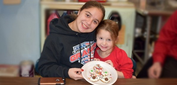 A Vestal High School student smiles for a photo with her little sister and the sister's decorated gingerbread man cookie at the Universal Pre-K at Cub Care's Cookie Decorating party on December 20, 2018