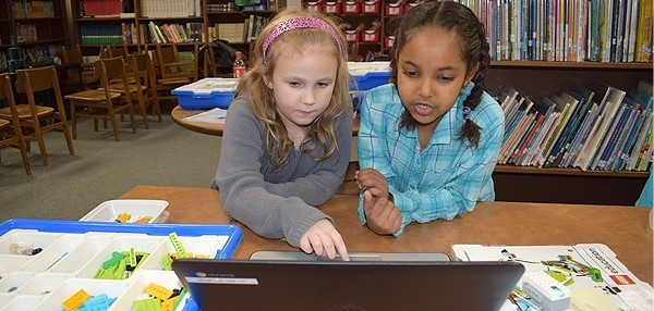 Two first-grade girls begin the steps of programming their Tadpole robot they built from WeDo 2.0 kits and help from Lockheed Martin Owego volunteers.
