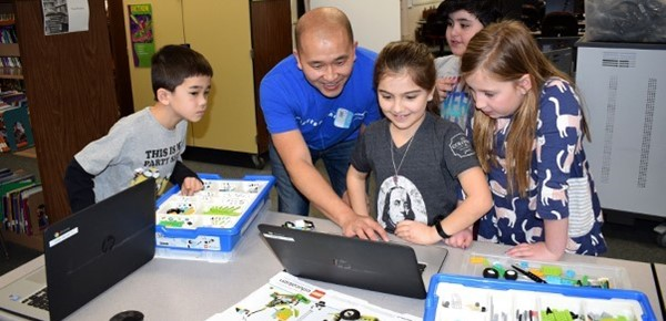 "A Lockheed Martin volunteer assists African Road Elementary second-graders as they begin the steps of programming a robot named ""Tadpole"" they just built out of a WeDo 2.0 L E G O  kit."