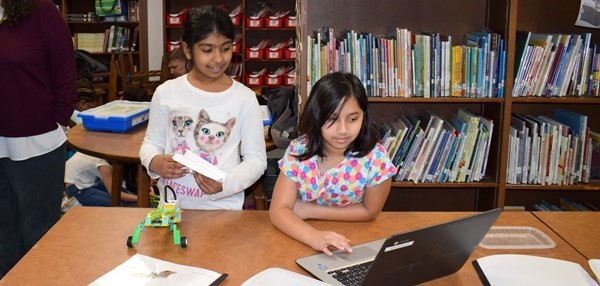 Two third-grade girls double check the instructions on their Chromebook to make sure they have completed all the steps to build their robotic paper airplane launcher.