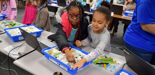 "Two second-grade girls reach for LEGO pieces as they work together to build a ""Tadpole"" robot in the African Road Elementary School library on February 23."