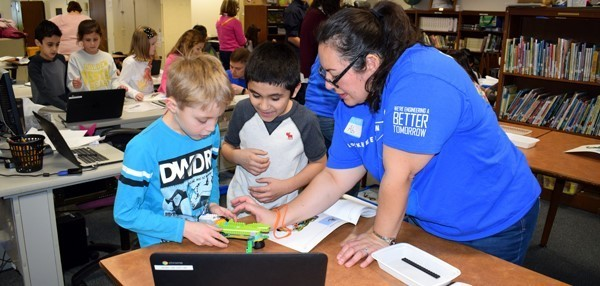 A Lockheed Martin volunteer helps two very excited third-graders as they build their robot in the African Road Elementary School library on February 23.