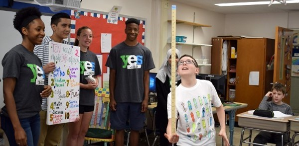 A Vestal Hills Elementary School fifth-grade boy balances a ruler on his hand as part of the YES Leads presentation by Vestal High School students that show how making safe decisions is easier when looking toward your future