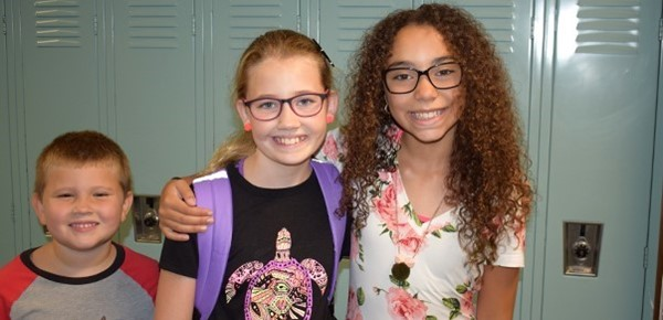 A first-grade little brother photo-bombs two sixth-grade girls in front of lockers at Vestal Middle School's Sixth-grade Orientation on August 27, 2018