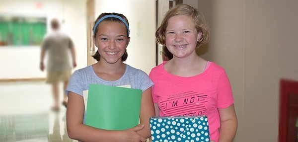 Two girls from the same elementary school smile together for a photo during Sixth-grade Orientation at Vestal Middle School on August 27, 2018