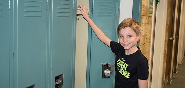 An incoming sixth-grade boy starts to stock his new locker with supplies during Orientation at Vestal Middle School on August 27, 2018