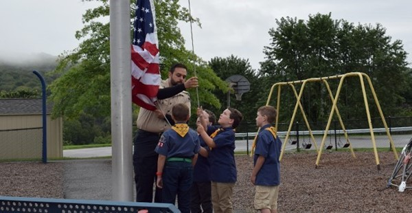 Cub Scouts from Troop 243 begin to raise the flag on the Glenwood Elementary School flagpole at the beginning of the Patriot Day ceremony on September 11, 2018