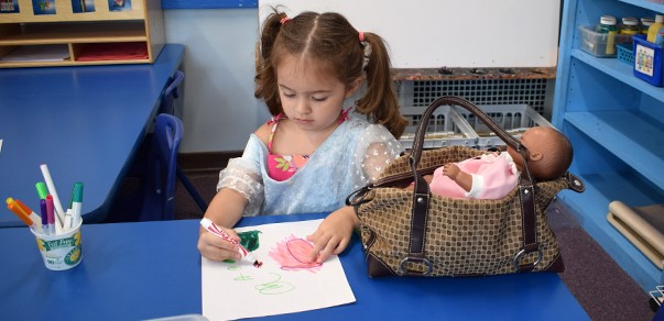 A girl in the Universal Pre-Kindergarten program at the Cub Care campus carefully colors her drawing during student orientation on September 5, 2018