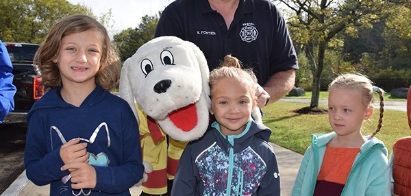 Three Kindergarten girls cuddle up next to Sparky the Fire Dog during a Fire Safety lesson at African Road Elementary School on October 8, 2019.