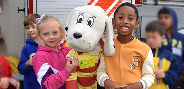 Two Vestal Hills Elementary students, a boy and a girl, hold Sparky during the Fire Safety lesson at their school on October 9, 2019.