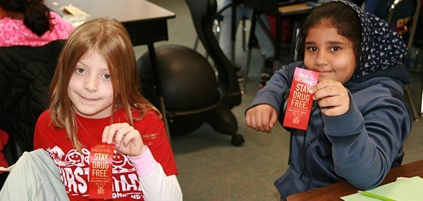 Two African Road Elementary School girls hold up their red ribbons that have the message Stay Drug-free... on Red Ribbon Day, October 18, 2019.