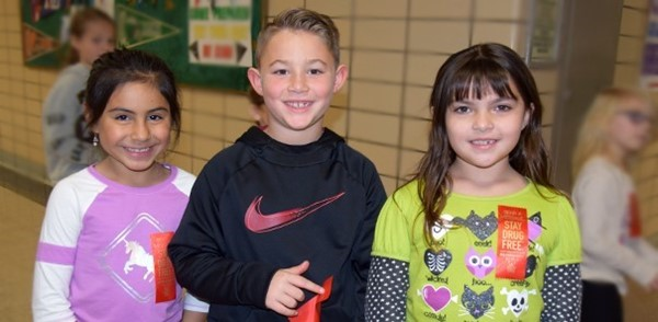 Three Clayton Avenue Elementary students, two girls and a boy, proudly wear the red ribbons they received on Red Ribbon Day, October 18, 2019.