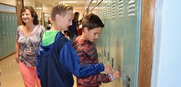 A sixth-grade boy helps a friend with his locker combination during Sixth-grade Orientation in August 2019.