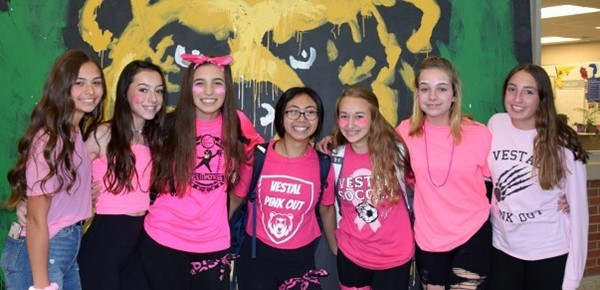 Seven Vestal High School girls, all dressed in pink shirts, stand for a group photo in front of the roaring bear mural in the lobby on All-Out Pink Out Day, October 17, 2019.