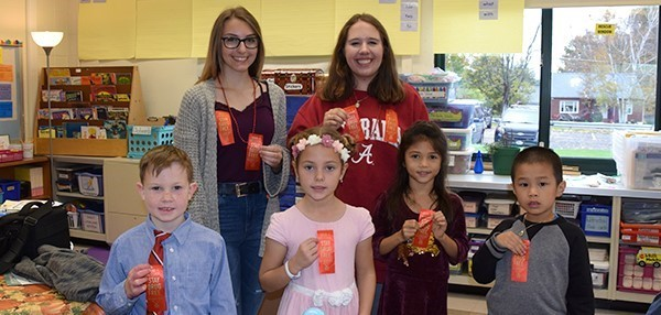 Four Glenwood Elementary second-grade students, two boys and two girls, proudly hold up red ribbons given to them by two Vestal High School students on Red Ribbon Day, October 18, 2019.