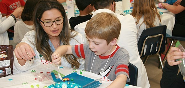 A Binghamton University pharmacy student watches a Vestal Hills Elementary second-grade boy count M and M candies with a white spoon on a blue pill-counter.