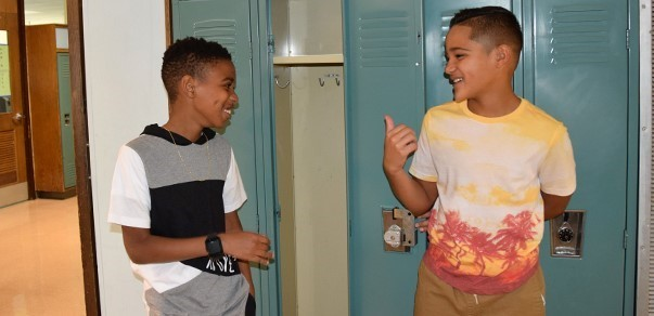 Two sixth-grade boys chat next to one's open locker during Vestal Middle School Orientation on August 26, 2019.