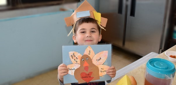 A boy from the Cub Care campus of the Vestal Universal Pre-Kindergarten program holds up a Thanksgiving placemat that he made for his family. The turkey feathers each show something that he is thankful for... During the Family Feast on November 26, 2019.