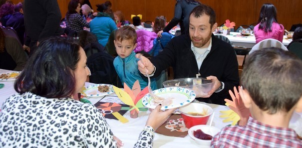 A father dishes up sliced turkey onto the plate of his wife during the Thanksgiving Feast at the Jewish Community Center campus of the Vestal Universal Pre-Kindergarten program on November 14, 2019.