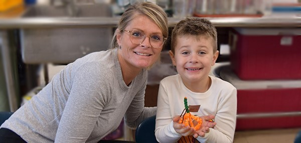 A mother and her son pose for a photo as he holds the orange pumpkin made out of beads he fashioned to decorate the table during the Universal Pre-Kindergarten Family Feast at the Cub Care campus on November 26, 2019.