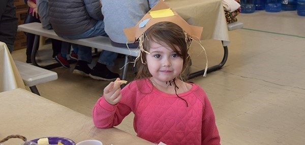 A little girl in paper Thanksgiving hat eats a piece of roll during the Family Feast at the Cub Care campus of the Universal Pre-Kindergarten program on November 26, 2019.