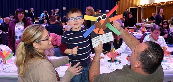 A mother and father steady their son who is standing between them with his paper turkey at the Universal Pre-Kindergarten class table during the Thanksgiving Feast at the Jewish Community Center on November 14, 2019.