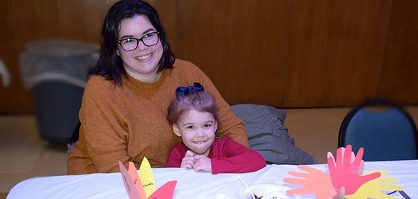 A mother and her daughter, a student in the Vestal Universal Pre-Kindergarten program, sit at a table waiting for the Thanksgiving Feast at the Jewish Community Center campus to begin on November 14, 2019.