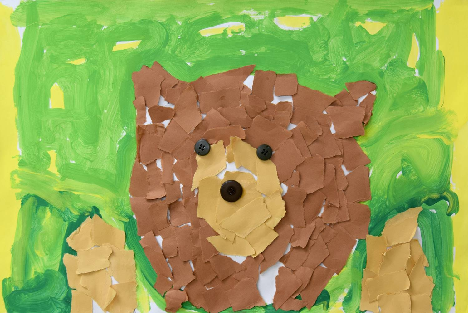 A brown bear made out of torn construction paper on a yellow and green background was created by Wil