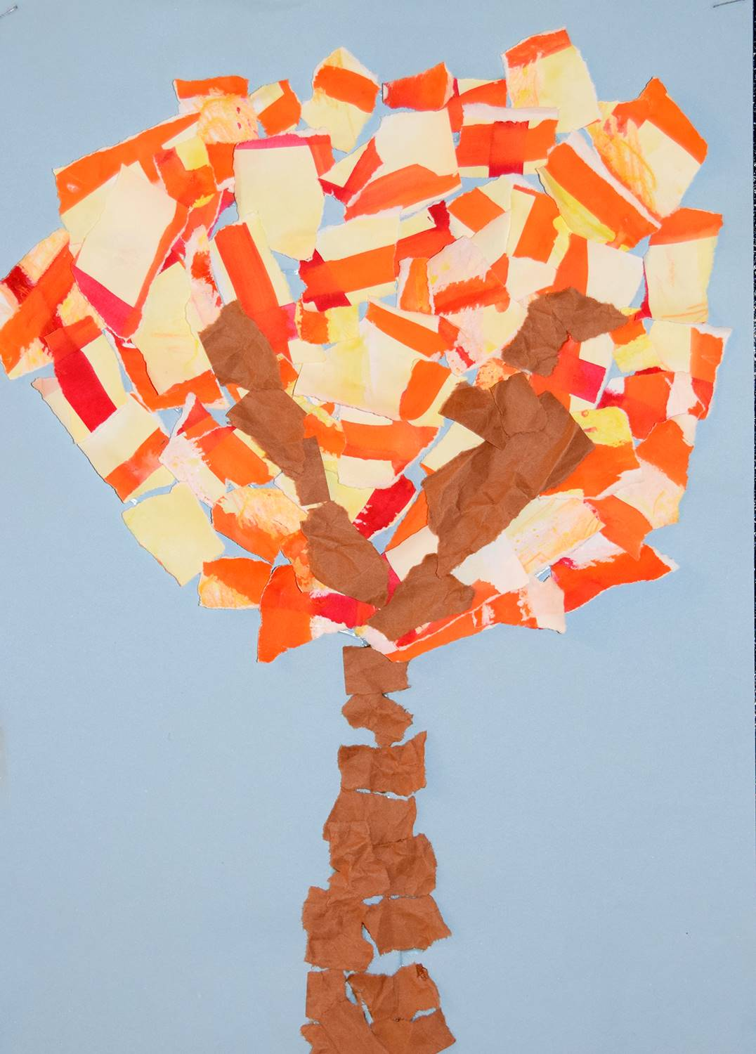 An autumn tree made out of torn construction paper on a blue background was created by Asher, an Afr