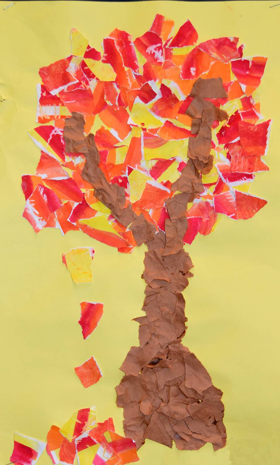 An autumn tree made out of torn construction paper on a yellow background was created by Cameron, an