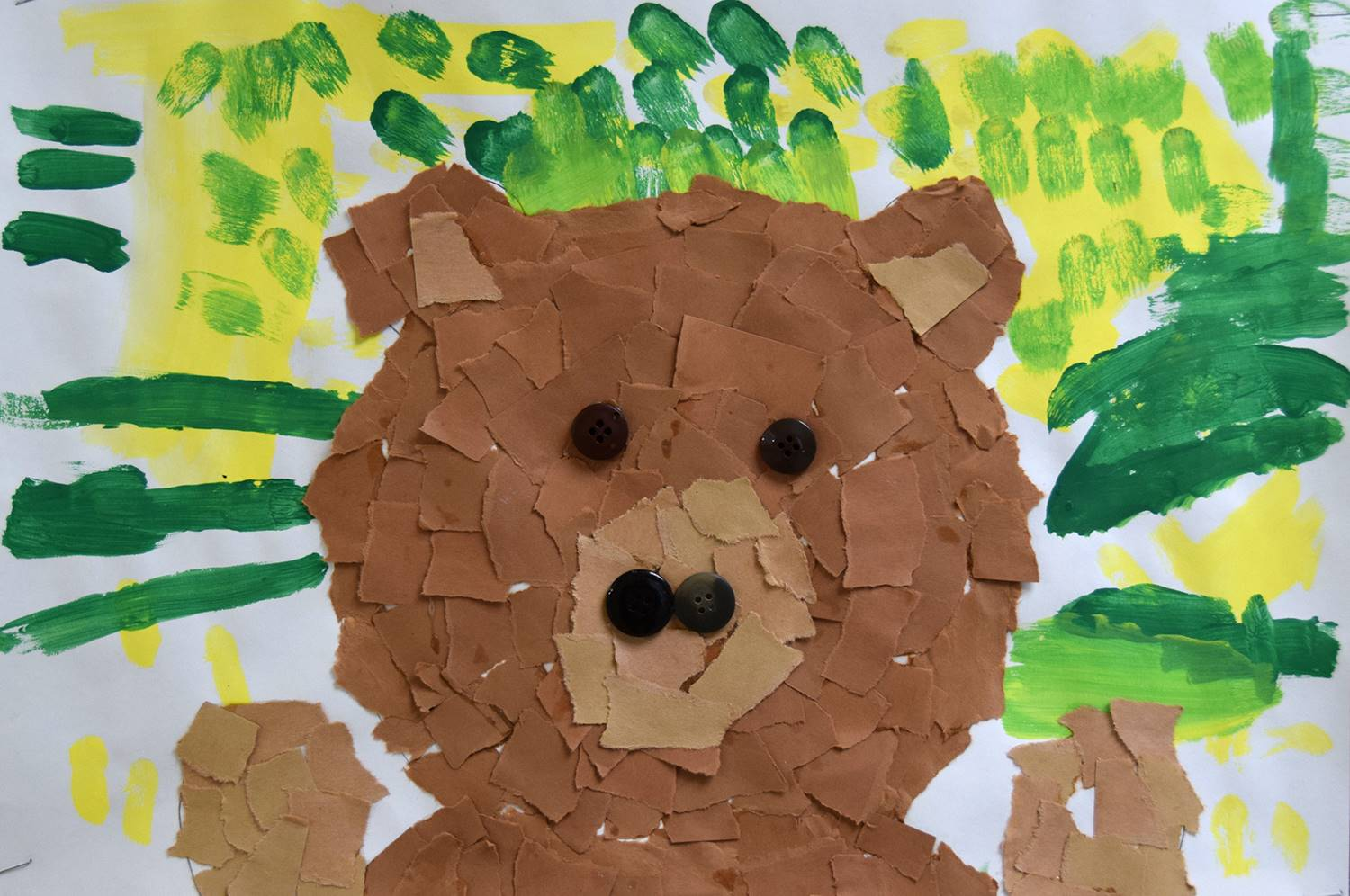 A brown bear made out of torn construction paper on a yellow and green background was created by Jos