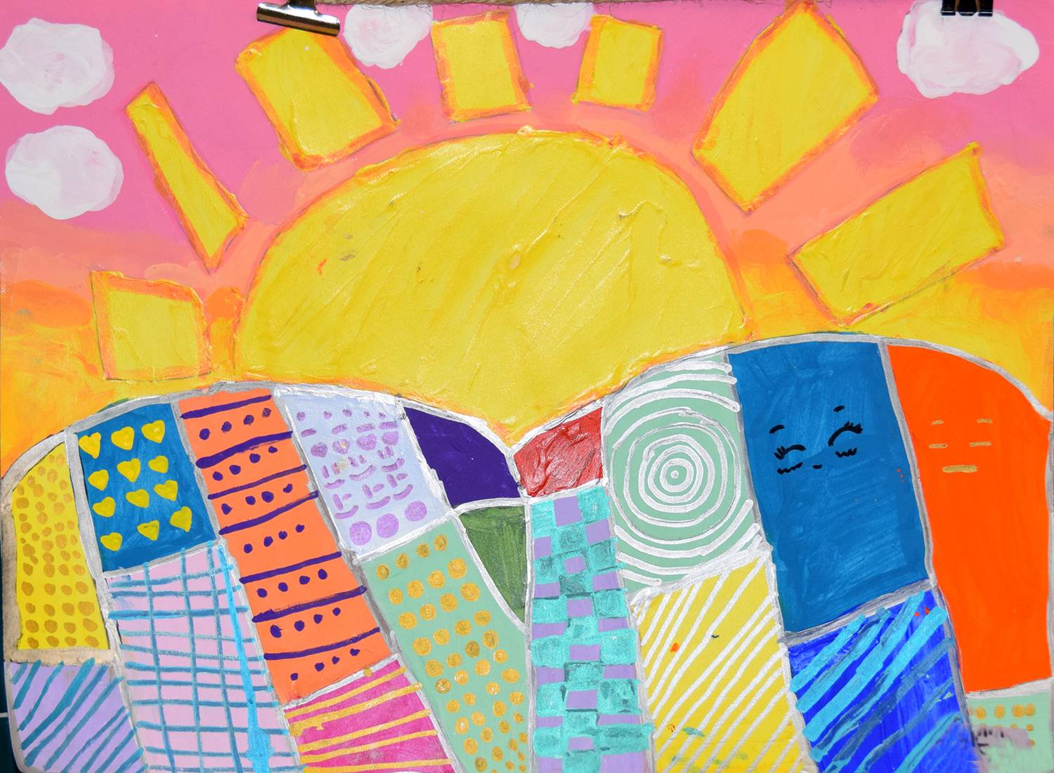 The sun rising over hills, which look like patchwork quilts. By KayLynn at Glenwood Elementary Schoo
