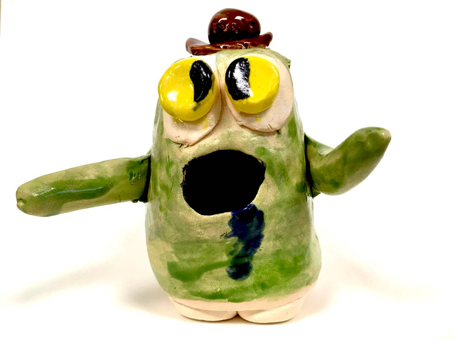 A green ceramic monster wearing a little brown derby hat, made by a Vestal Middle School student