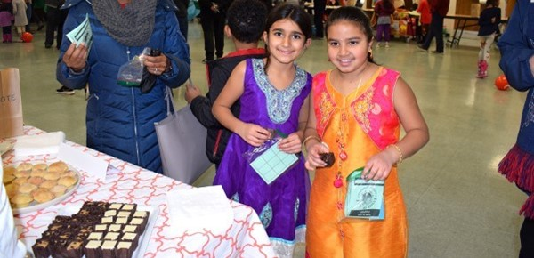Two African Road Elementary girls in traditional Indian saris enjoy goodies from the French table during the school's Taste of A R E  event on January 16, 2019.