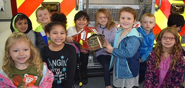 First-graders from Clayton Avenue Elementary School gather for a group photo at the back of a Vestal fire truck in the garage at Fire Station 1 during their annual fire safety lesson in October 2018.