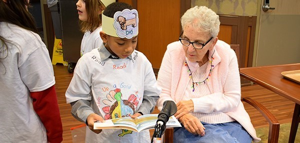 A second-grade Glenwood Elementary School boy reads his book to a Vestal Park Nursing and Rehabilitation resident at her facility after a Readers Theater presentation on December 18, 2018.
