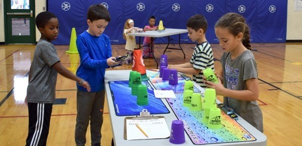 Two boys and two girls stack cups at one of the stations during the Cup-stacking Challenge in their physical education class in the Vestal Hills Elementary School gym.