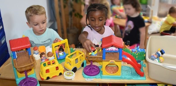 A boy and a girl find a Little People playset to share in their Universal Pre-Kindergarten classroom at the Jewish Community Center (during Orientation on September 4, 2018)