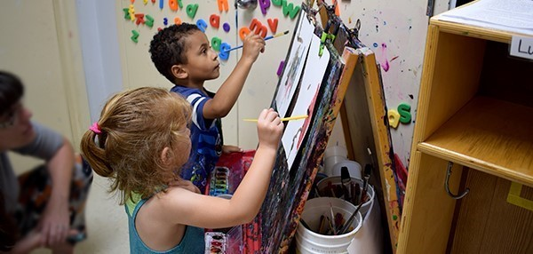 A boy and a girl paint side-by-side on easels in their Universal Pre-Kindergarten classroom during Orientation at the Jewish Community Center campus on September 4, 2018