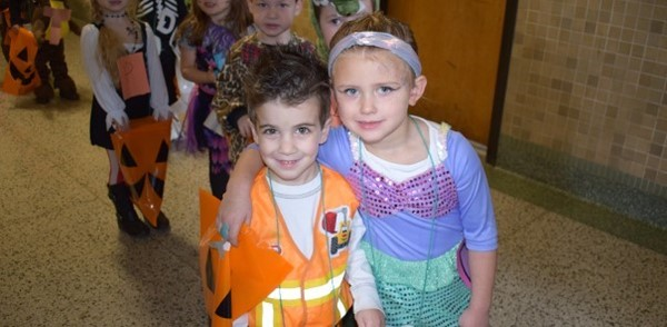 Two Universal Pre-Kindergarten students, a boy and a girl, are dressed for their class' cultural celebration of Halloween.