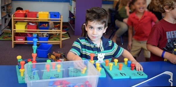 A boy plays with counting pegs during the Universal Pre-Kindergarten orientation at the Jewish Community Center campus in September 2018.