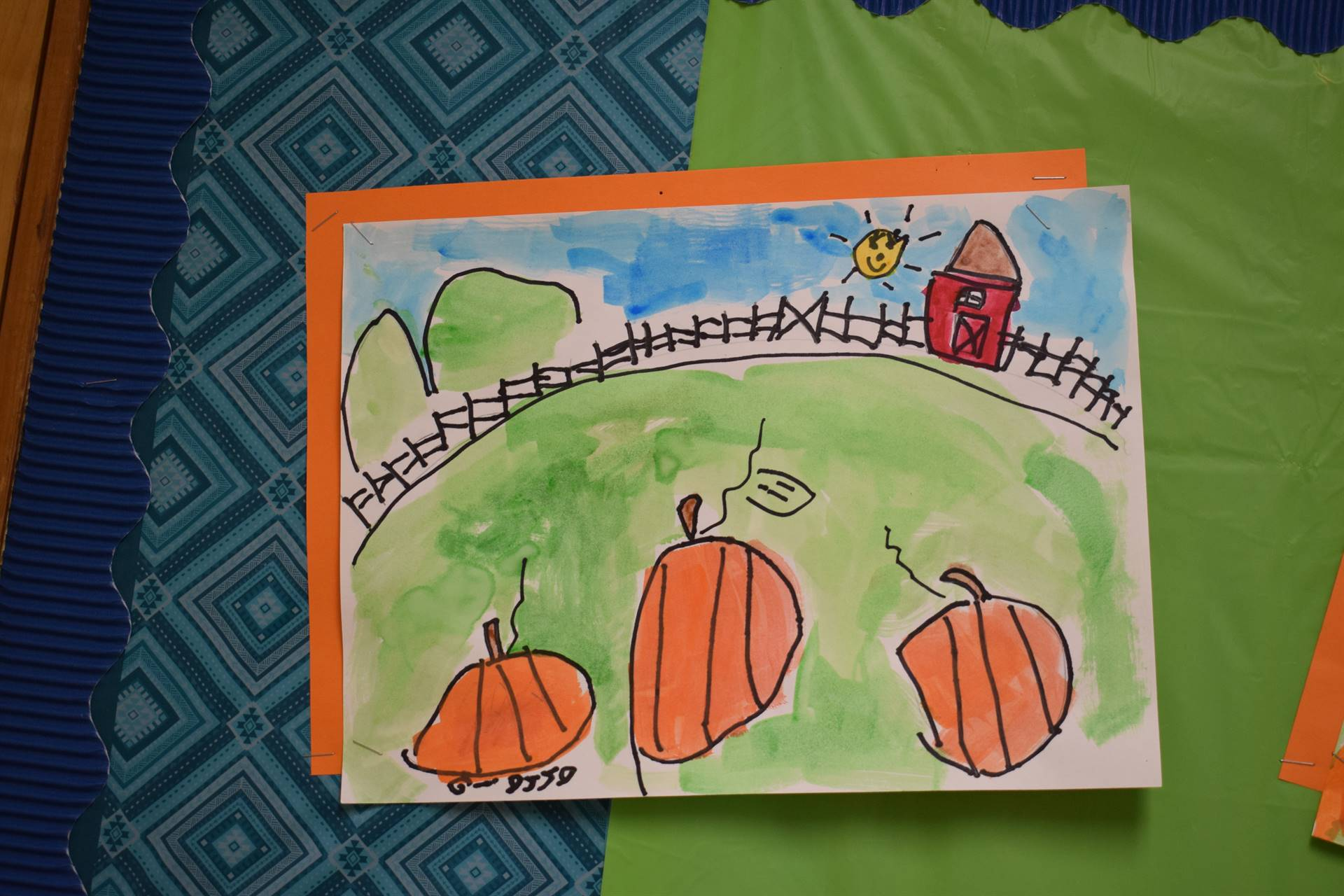 Three little pumpkins in a field with blue sky, happy yellow sun, brown fence and red barn in the ba