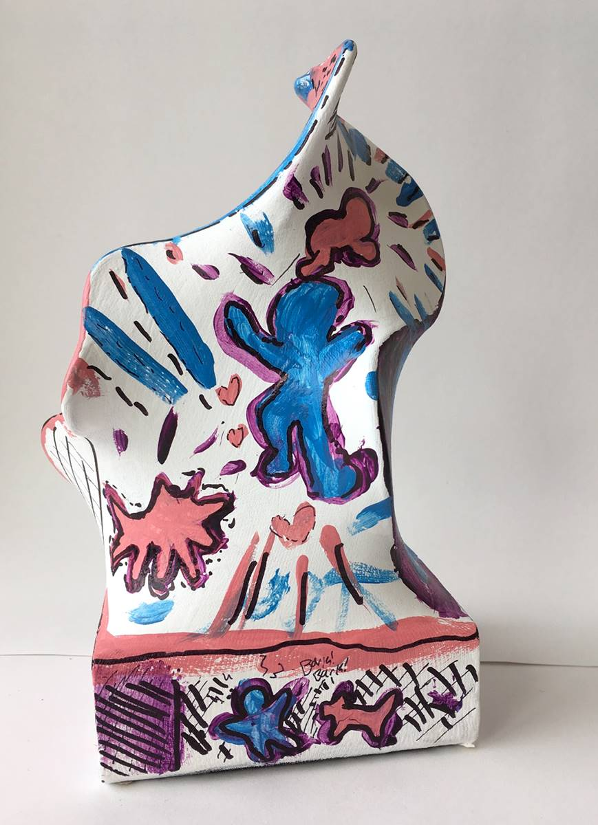 White abstract sculpture with pink and blue figures painted on it.