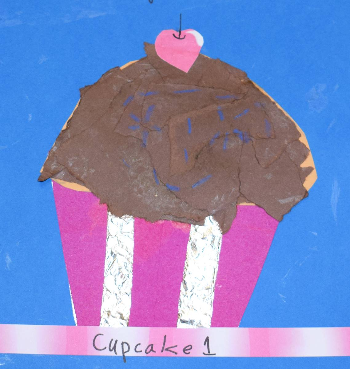 A mixed media artwork of a chocolate cupcake with red cherry on top in a pink and silver wrapper.